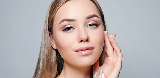 stock image of a female model smiling by holding hand on face