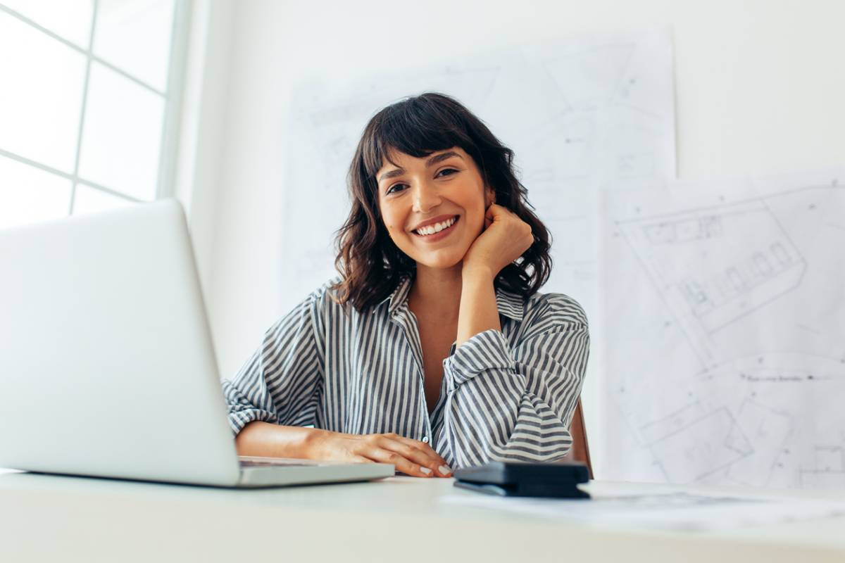 Woman on computer comparing before and after photos.