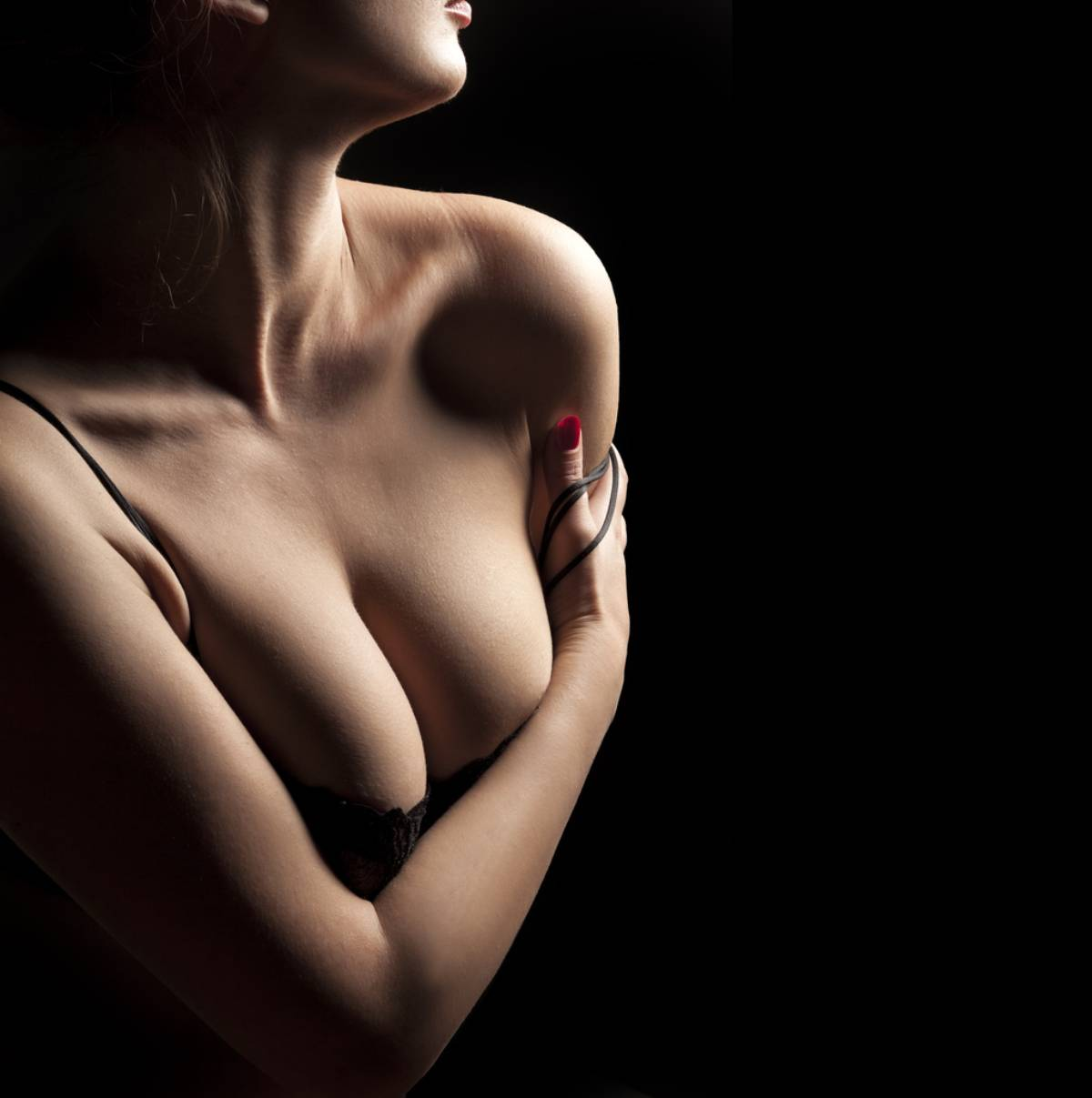 Woman in shadow with breast asymmetry.